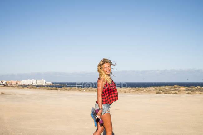 Linda loira jovem posando com skate ao ar livre — Fotografia de Stock