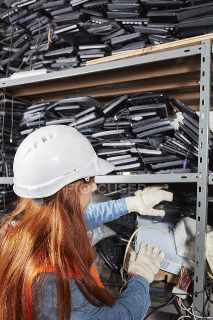 Female worker in computer recycling sorting shelf — Stock Photo