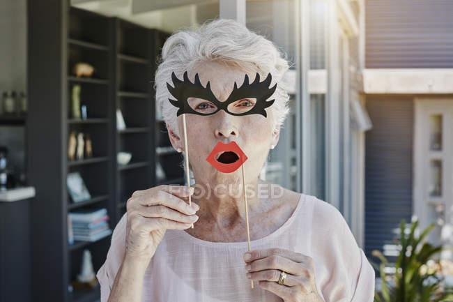 Femme âgée se cachant derrière des masques en papier — Photo de stock