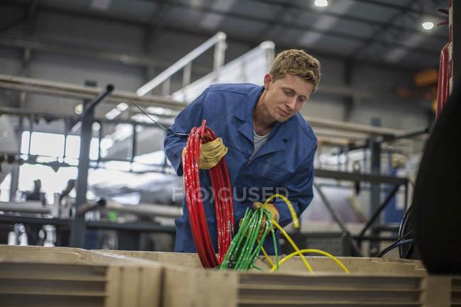 Arbeitnehmer, die durch bunte Drähte in Werkstatt suchen — Stockfoto
