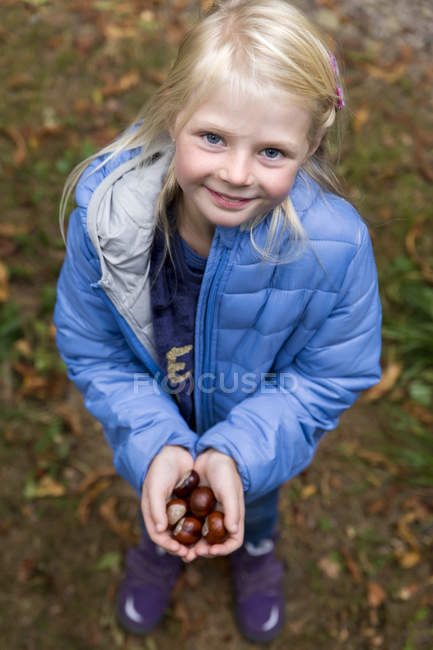 Portrait of smiling blond little girl holding chestnuts in her hands — Stock Photo