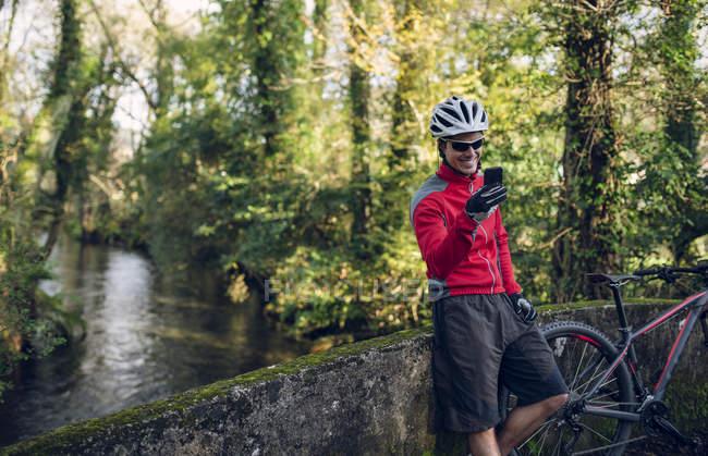 Mountain bike utilizzando smartphone in natura — Foto stock