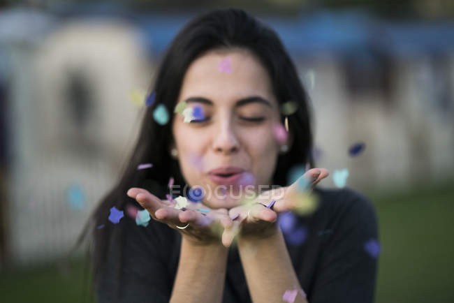 Happy young woman blowing confetti outdoors — Stock Photo