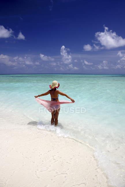 Maldivas, mulher em pé na água rasa — Fotografia de Stock
