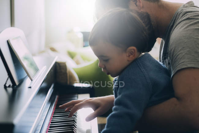 Enfant et père jouant piano ensemble — Photo de stock