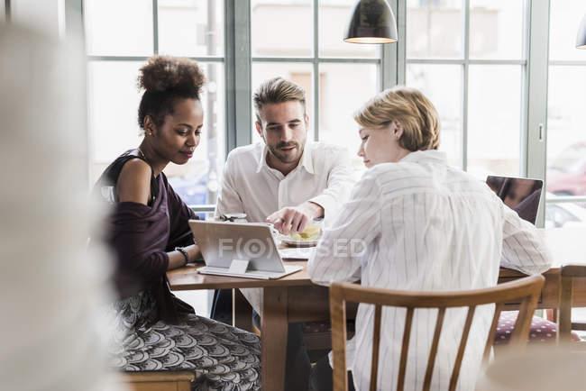 Трое молодых людей, используя таблетки в кафе — стоковое фото