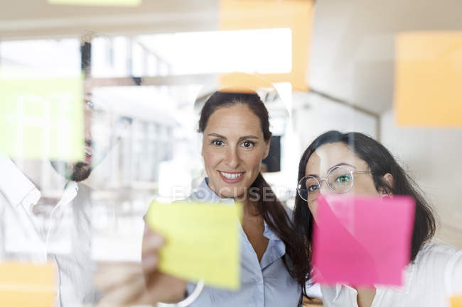 Colleagues in modern office working with adhesive notes — Stock Photo
