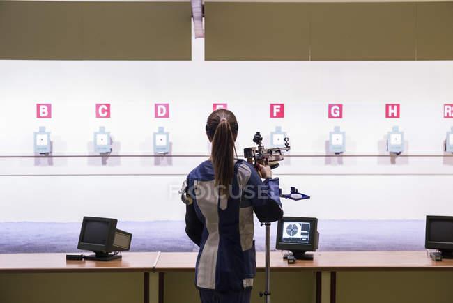 Mulher na sua frente os alvos em um campo de tiro — Fotografia de Stock