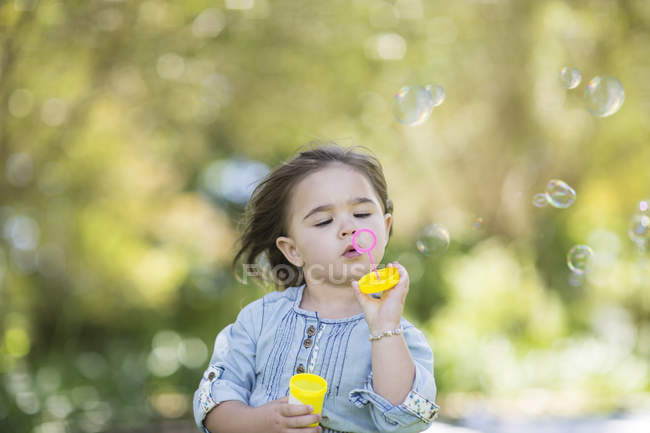 Baby girl blowing bubbles outside garden park — Stock Photo