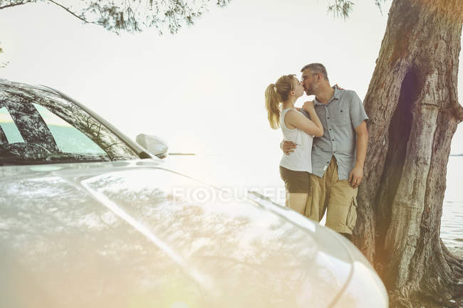 Couple on a road trip taking a break kissing each other — Stock Photo