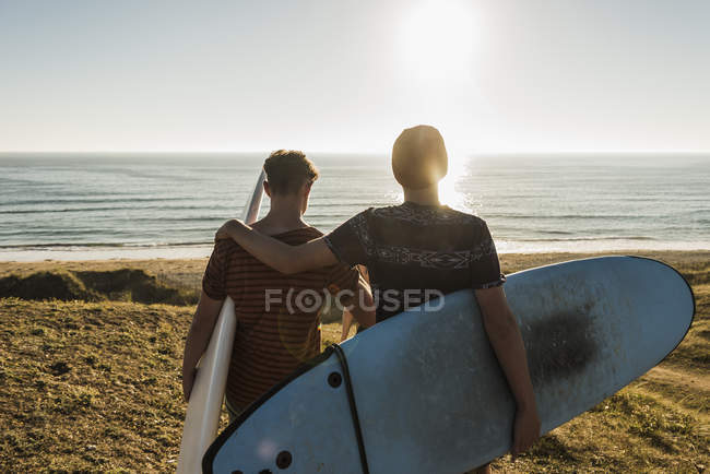 Two friends with surfboards walking at seaside — Stock Photo