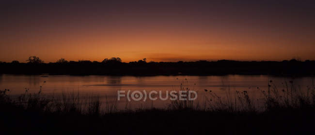 Namibia, sunset at Okavango over field and lake — Stock Photo