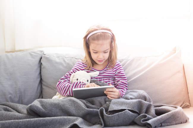 Portrait de petite fille assise sur le canapé et utilisant une tablette — Photo de stock