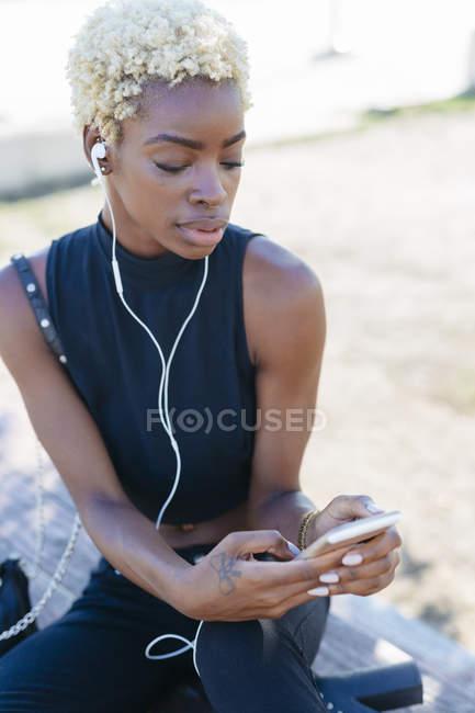 Giovane donna africana con cellulare e auricolari — Foto stock