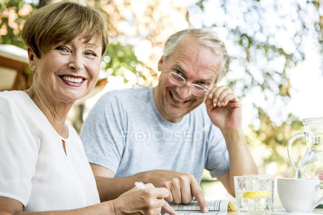 Senior couple sitting in garden by the table looking at camera smiling — Stock Photo