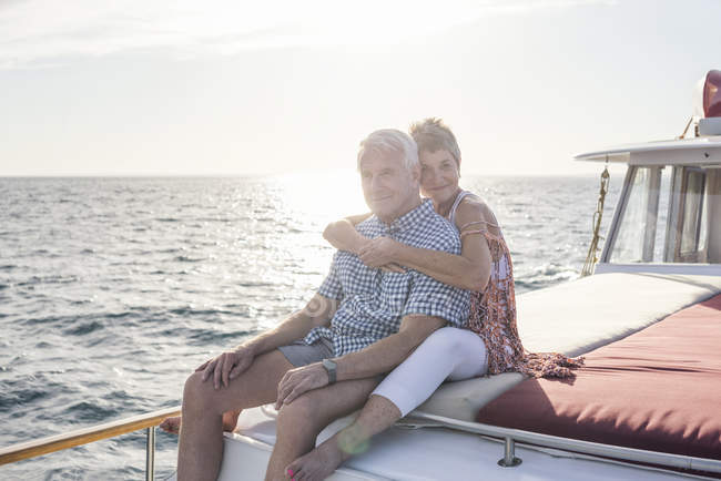 Affectionate couple on boat trip hugging and looking at camera — Stock Photo