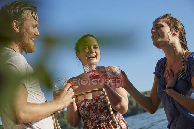 Amigos felizes em um lago, tomando uma bebida — Fotografia de Stock