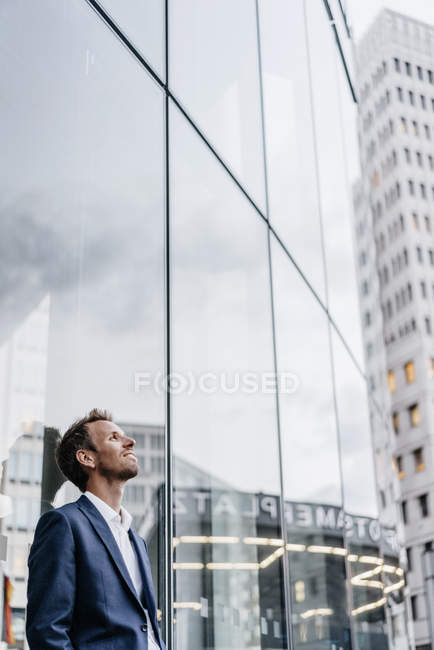 Hombre de negocios que se inclina contra la fachada de cristal en la ciudad de - foto de stock