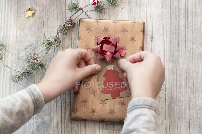 Mãos de menina, embrulho de presente de Natal — Fotografia de Stock