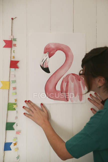 Artist watching her aquarelle of a flamingo — Stock Photo