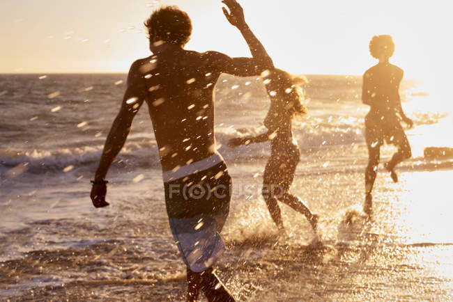 Playful friends on the beach at sunset — Stock Photo