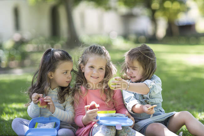 Three baby girls sharing food together outside garden park — Stock Photo