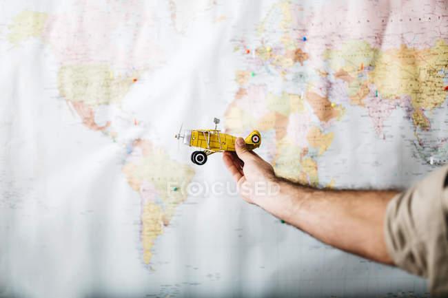 Человек, держащий самолета перед словом карта — стоковое фото