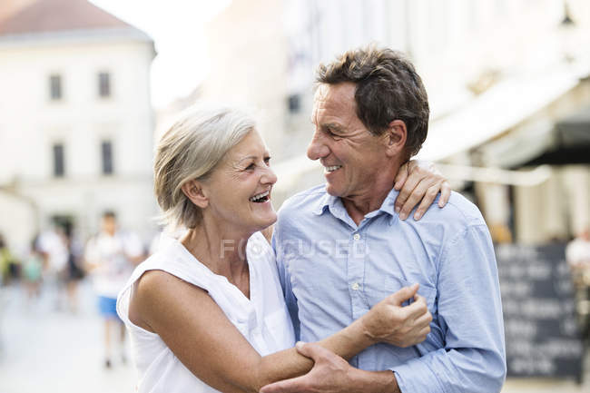 Happy senior couple walking in city — Stock Photo