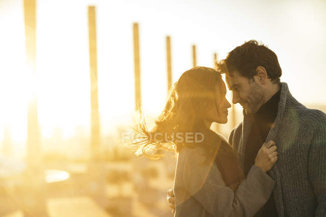 Happy affectionate couple in love standing at backlit — Stock Photo