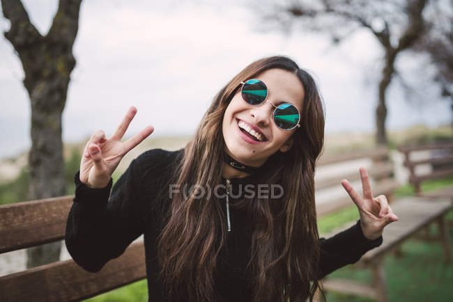 Portrait of young woman wearing mirrored sunglasses showing victory signs — Stock Photo