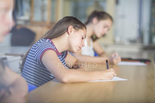 Allievi femminili scrittura durante test di classe — Foto stock