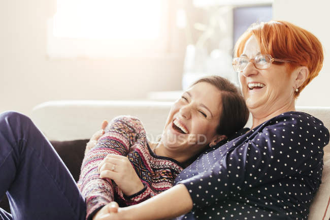 Mother and adult daughter laughing sitting on couch — Stock Photo