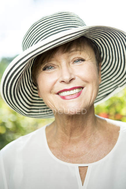 Portrait of smiling senior woman in hat looking at camera — Stock Photo