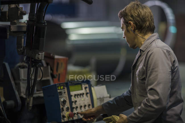 Worker operating machinery at control panel in factory — Stock Photo
