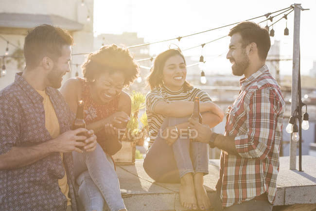 Friends at rooftop party in bright sunlight — Stock Photo