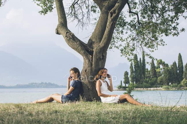 Itália, Lago de Garda, duas mulheres jovens, encostado a uma árvore falar em telefones celulares — Fotografia de Stock