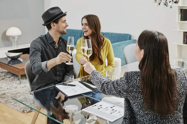 Portrait of couple toasting with shop assistant — Stock Photo