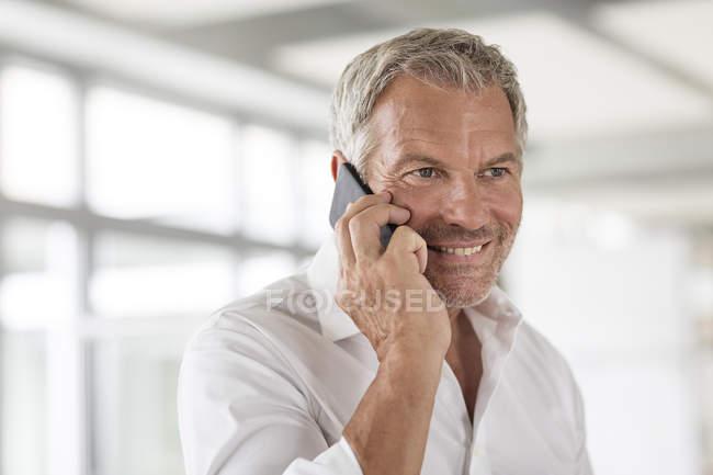 Uomo d'affari al cellulare in ufficio — Foto stock