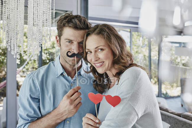 Couple with paper moustache and heart-shaped eye disguise — Stock Photo