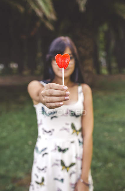 Young woman holding heart-shaped lollipop — Stock Photo