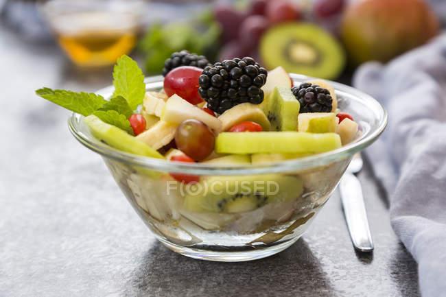 Ensalada de frutas con moras en un bol - foto de stock