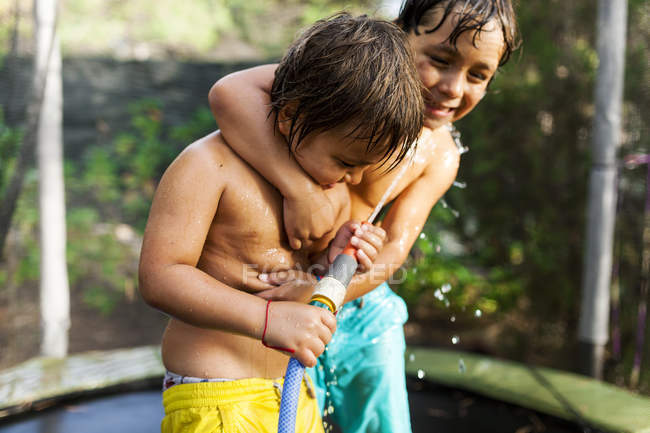 Two little brothers playing with a water hose on a trampoline — Stock Photo