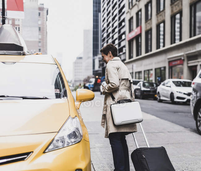 Woman standing at taxi in Manhattan, New York City, USA — Stock Photo