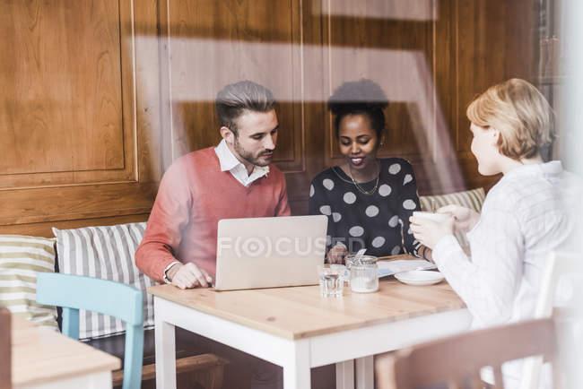 Трое молодых людей, проводящих собрание в кафе — стоковое фото
