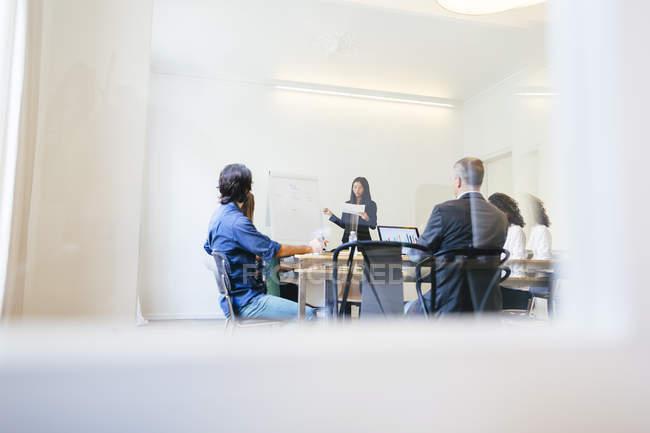Negócios tendo uma reunião de equipe atrás de portas de vidro — Fotografia de Stock