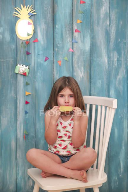 Little girl sitting on chair eating lemon ice lolly — Stock Photo