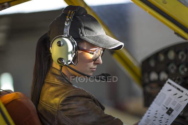 Молодая женщина-пилот осматривает кабину самолета — стоковое фото