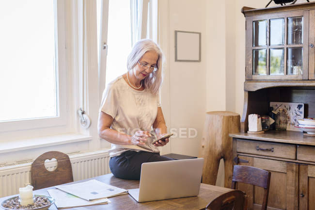 Businesswoman working at home office with smartphone and laptop — Stock Photo