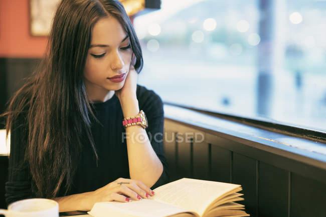 Junge Frau in einem Café sitzen und ein Buch zu lesen — Stockfoto