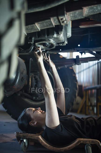 Female mechanic working at fire brigade workshop, lying on creeper — Stock Photo